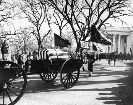 """John F. Kennedy's funeral procession leaves the White House on the way to St. Matthew's Cathedral on Nov. 25, 1963. A color guard holding the presidential colors, and the riderless horse, """"Black Jack,"""" follow behind. Photo by Abbie Rowe"""