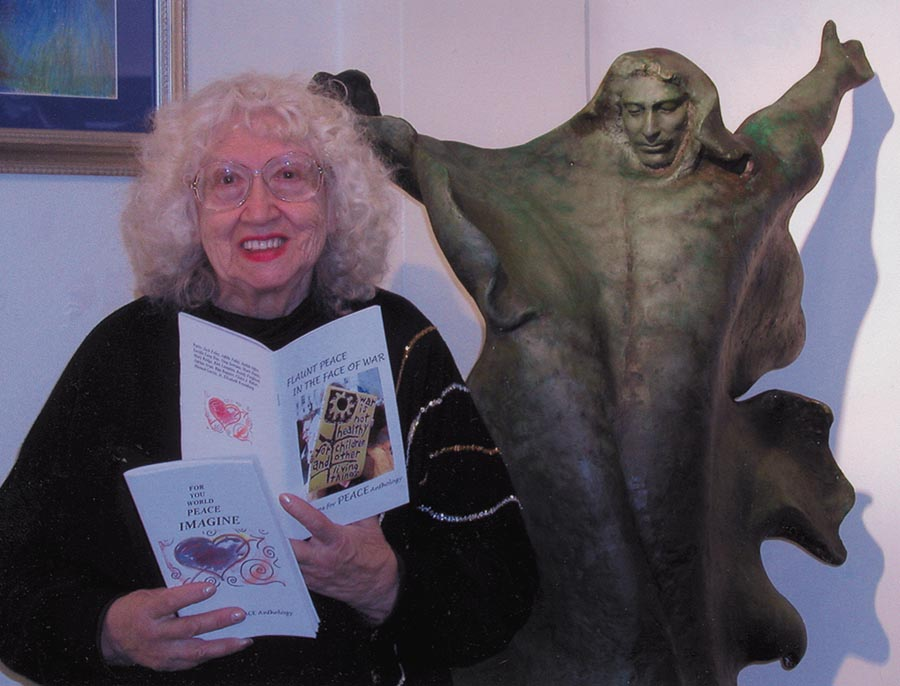 Mary Rudge, the late poet laureate of the city of Alameda, holds up peace leaflets next to the statue of another peace activist, St. Francis of Assisi. by sculptor Harriet Moore.