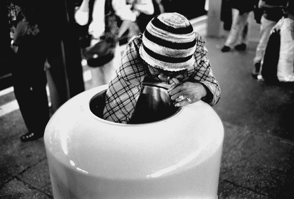 """A woman searches for a meal in a trash can, ignored by the crowds. Photo credit: """"One American Reality"""" by Dong Lin"""