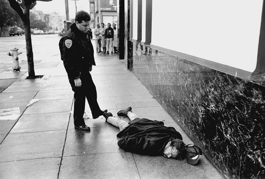 A policeman tries to nudge awake a homeless man on the streets of San Francisco, but the man cannot be awakened. Photo by Dong Lin from his book One American Reality.