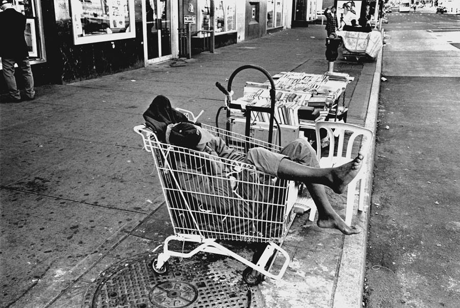 An empty shopping cart becomes a bed for a homeless man in a consumer society. New York City. Photo by Dong Lin from his book One American Reality.