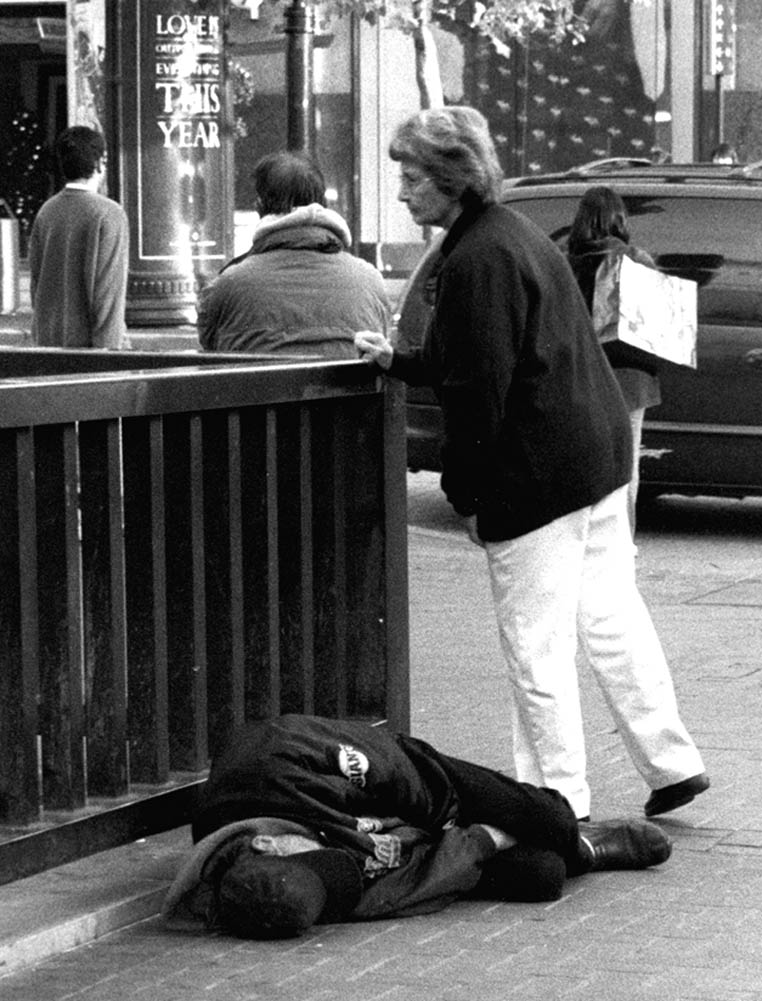 As poverty has become so widespread in San Francisco, passers-by have grown accustomed to ignoring homeless people lying on the sidewalk. Photo by Lydia Gans