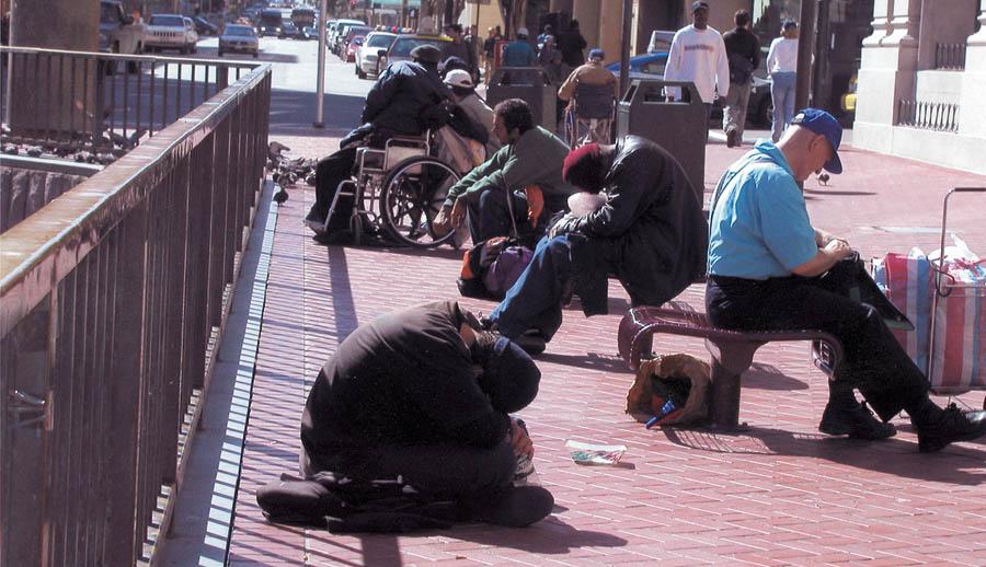A row of homeless men sitting on a San Francisco sidewalk. Photo by Lydia Gans