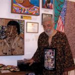 "Arnold White in his Oakland gallery stands next to a mosaic tile portrait of his mother (at left) and his magnificent painting, ""Freedom Tree"" (at right). Lydia Gans photo"