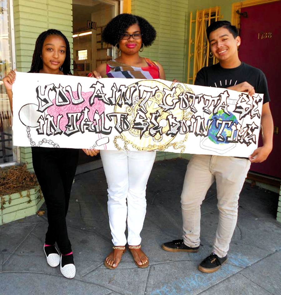 """Young artists Alasia Ayler, Brianna Pierce and Vernon Neely display their artistic statement: """"You ain't gotta be in jail to be doing time."""" Lydia Gans photo"""
