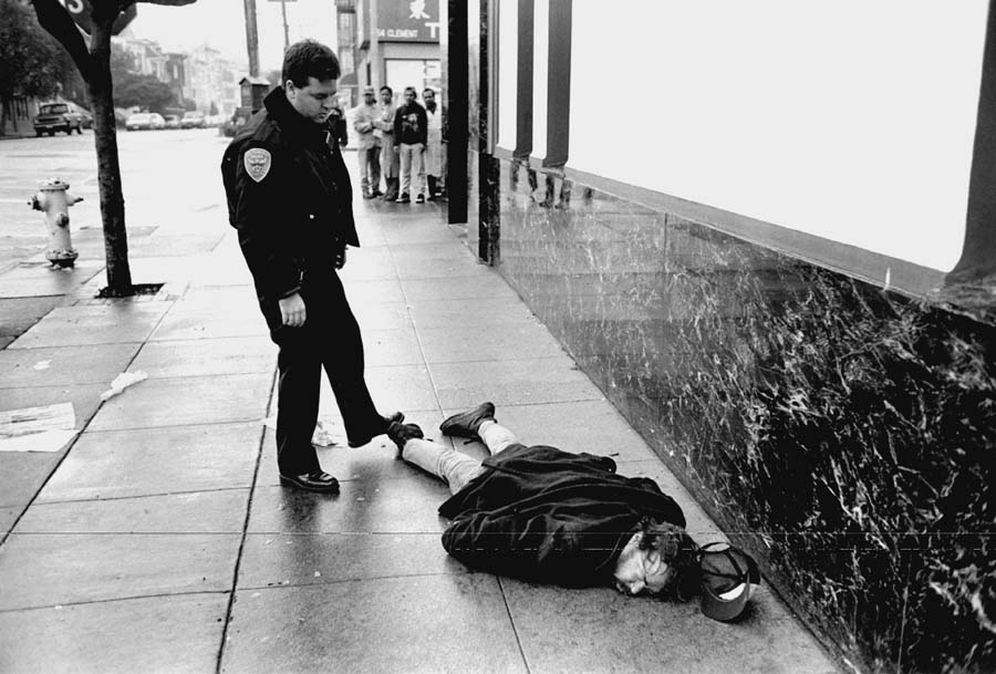 In Dong Lin's photoessay on homelessness, One American Reality, a policeman finds a homeless man dead on a San Francisco sidewalk. Dong Lin photo