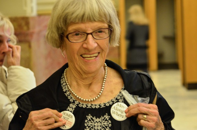 "Billie Bramhall with a ""Move Along to Where?"" button. In the background, an advocate of the bill weeps. Photo by Tessa Cheek."