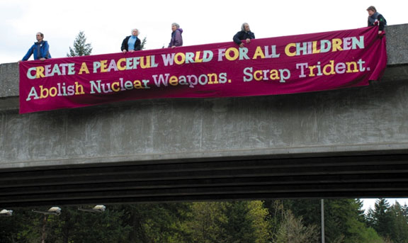 """Trident protesters on a freeway overpass: """"Create A Peaceful World For All Children. Abolish Nuclear Weapons. Scrap Trident."""" Photo courtesy Ground Zero Center"""