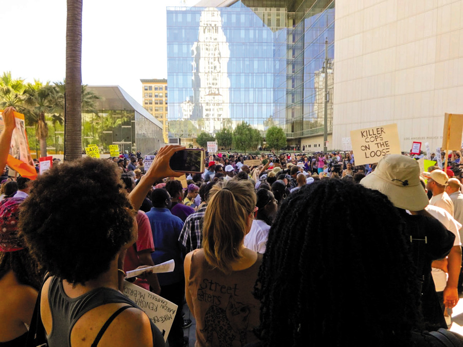 A Los Angeles protest of the police killings of Ezell Ford and Michael Brown held at the LAPD headquarters on August 17, 2014. A demonstrator records the protest. Videos are now a powerful tool to document police violence. Craig Dietrich photo
