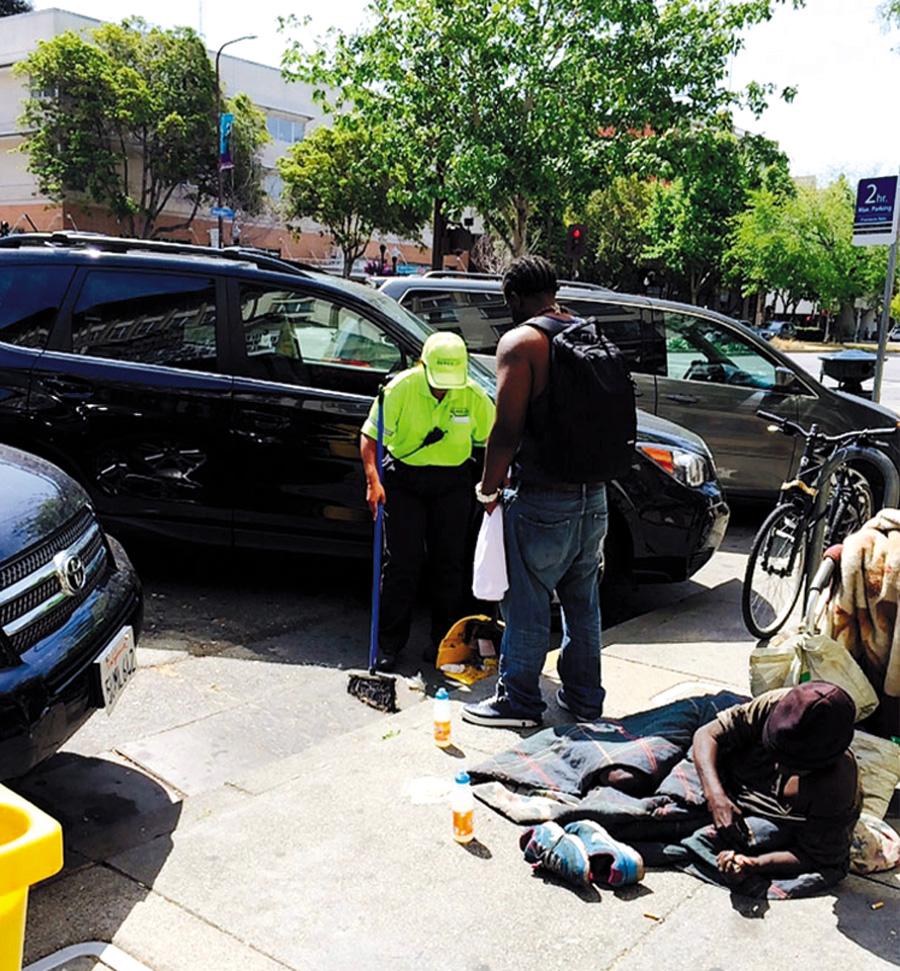 A DBA Ambassador literally tries to sweep away homeless people in downtown Berkeley, and then ordered the homeless men to leave the area. Carol Denney photo