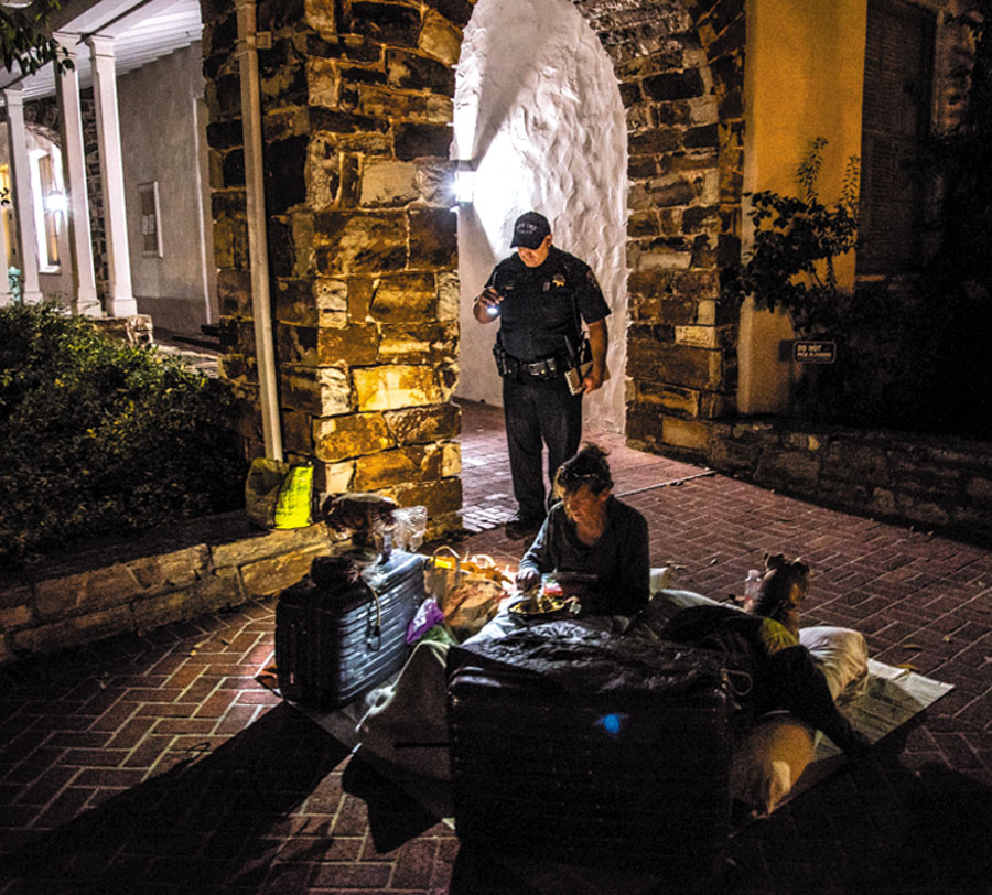 """The Santa Cruz police interrupt the sleep of a protester in the middle of the night to issue a citation for a """"sleep crime."""" Photo by Alex Darocy, Indybay.org."""