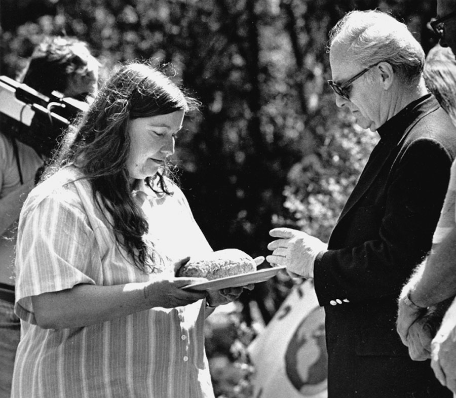 Shelley Douglass shares bread with Archbishop Raymond Hunthausen at peace vigil on the railroad tracks at the Bangor Naval Base, in protest of Trident submarines.