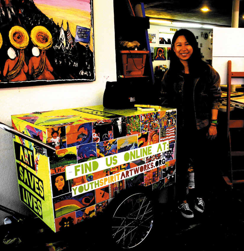 """Lia Li displays an """"art cart"""" used by young artists working at Youth Spirit Artworks.  Carol Denney photo"""