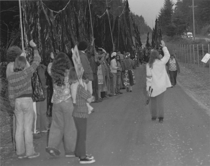"""After cutting through the fence at the Trident naval base, peace activists take the """"Trident Monster"""" inside the base.  Shelley Douglass is on the right, walking away from the camera, holding the bolt cutters.  Several children helped carry the monster over the fence."""
