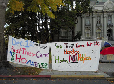 """""""First They Came for the Homeless."""" An eye-catching banner hangs in front of the occupation on Martin Luther King Street in front of Berkeley City Hall. Lydia Gans photo"""