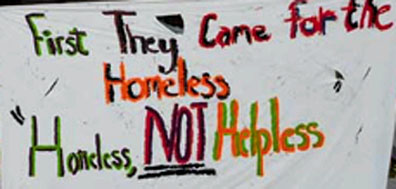 """A sign at the City Hall occupation warns:: """"First They Came for the Homeless."""""""