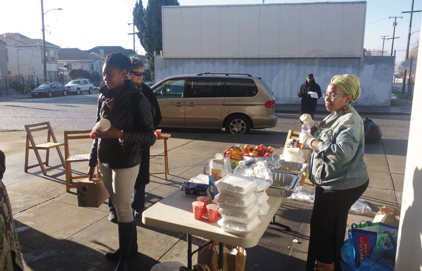 Denise, Delene (with coffee and cups), and Jovelyn set up their table at a homeless encampment in Oakland and began serving meals. Next, the women walked down the street serving breakfast and hot coffee. Wanda Sabir photo