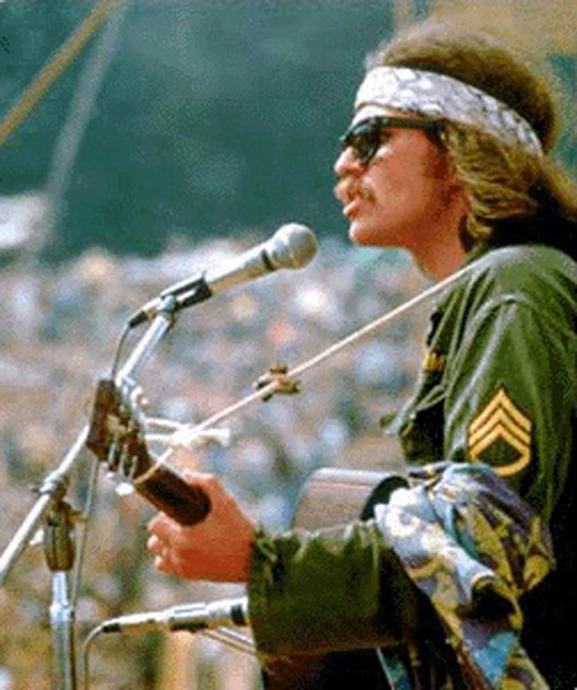 """Country Joe McDonald sand """"I Feel Like I'm Fixin' to Die rag"""" during his solo set before hundreds of thousands of people at Woodstock."""