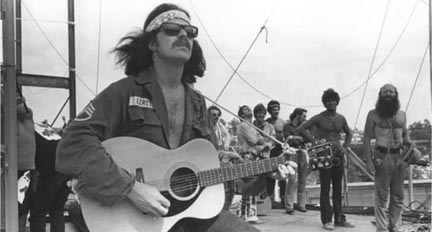 """Country Joe McDonald plays for 300,000 people at Woodstock. He said, """"They found a guitar, a Yamaha FG 150, and tied a rope on it (see the photo) and pushed me on stage. The rest is history."""" Photo credit: Jim Marshall"""