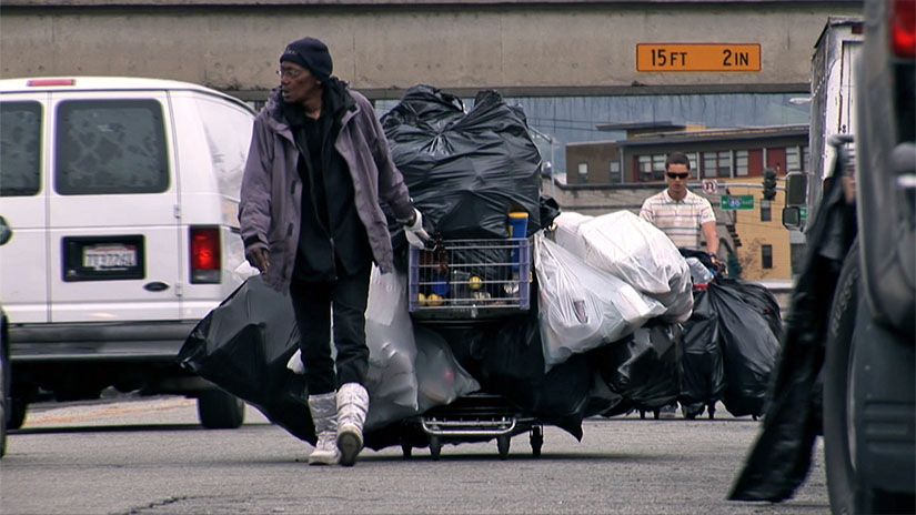 A recycler hauls a heavy load on the streets of West Oakland in this scene from Dogtown Redemption.