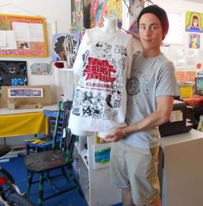 Brandon Pritzkat displays a t-shirt created by young artists to sell on the streets of Berkeley.