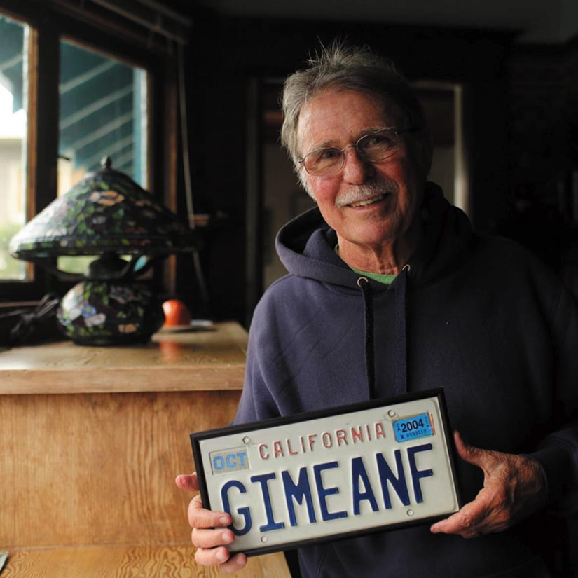 """Country Joe McDonald smilingly displays his """"Give Me an F"""" license plate."""