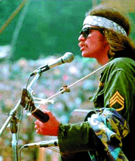 "Country Joe McDonald sings ""Next stop is Vietnam"" with 300,000 people at Woodstock."