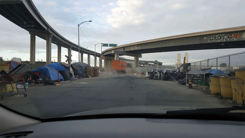 A homeless encampment under Oakland freeways, viewed through a car's windshield. Carts, tents and belongings are clustered on the left and right. Kwalin Kimaathi photo