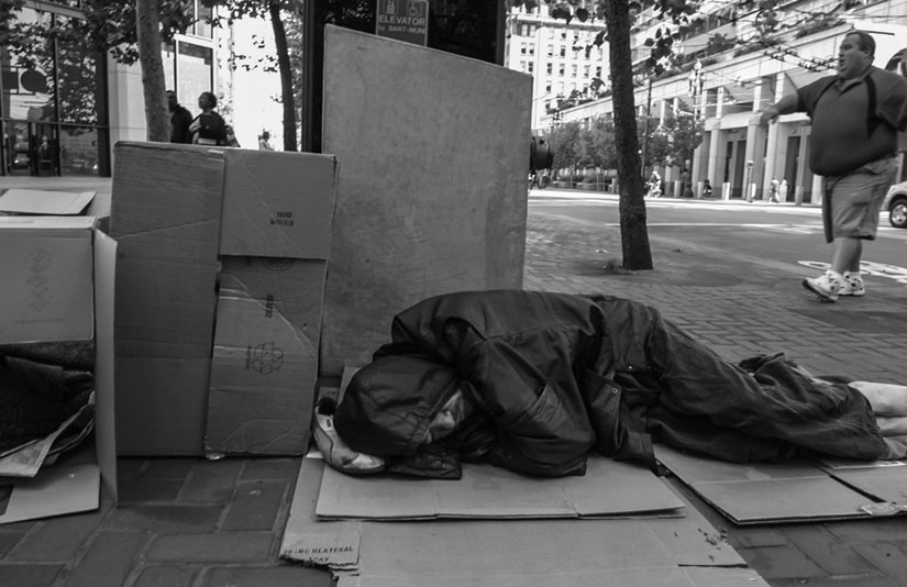 A homeless man sleeps on a San Francisco sidewalk as passers-by ignore him and pretend he's not even there. David Bacon photo