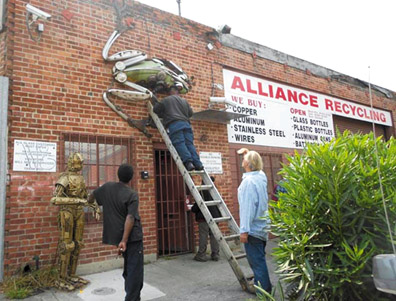 Workers take down the beautiful metal frog sculpture as Alliance Recycling closes its doors for the last time. Lydia Gans photo