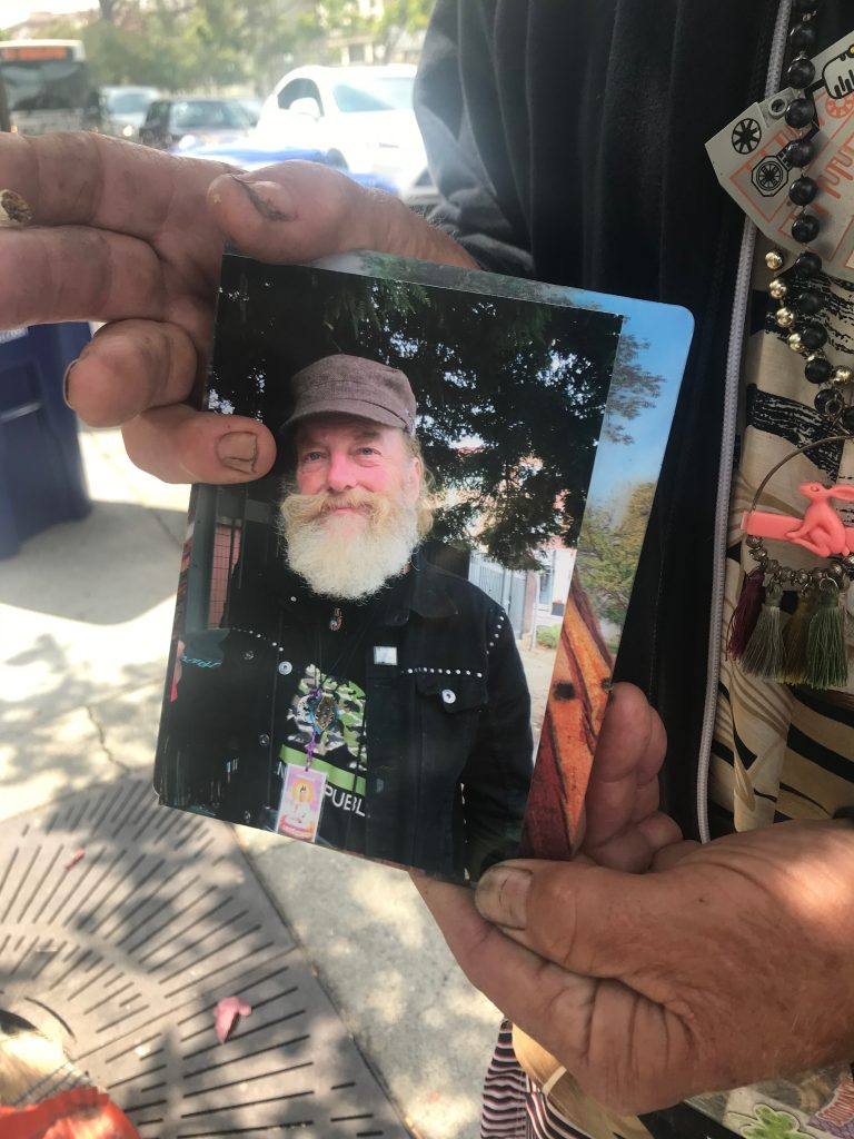 Douglas Freitag holds up a photo of himself.
