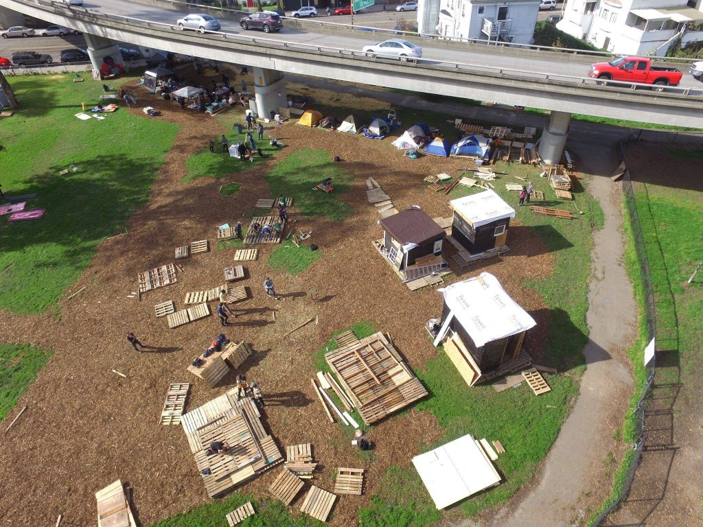 An arial view of the encampment being built. Three tiny homes and several tents stand together on a plot of land. Around them, wood pallets sit where new tiny homes will be built.