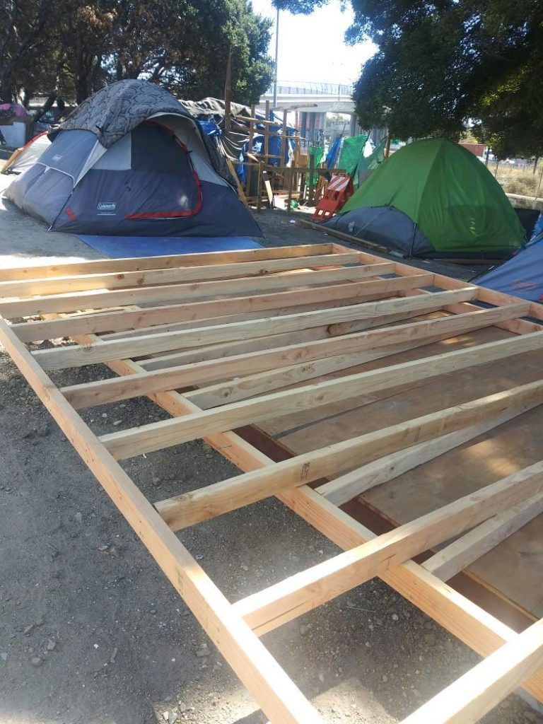 The photo depicts construction of supports in between tents at a homeless encampment in East Oakland