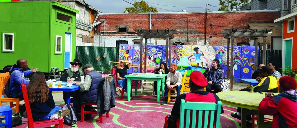 Street Spirit vendors and staff sit outside together sharing a picnic.