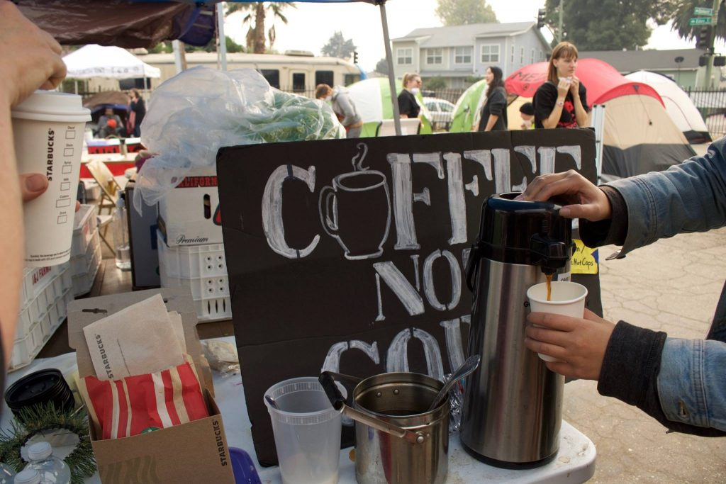 "A sign reads ""coffee not cops"" in front of a coffee dispenser. Encampment supporters pour coffee on the day of the eviction."