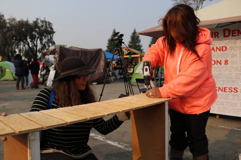 Volunteers help build structures for HDV residents to live in.
