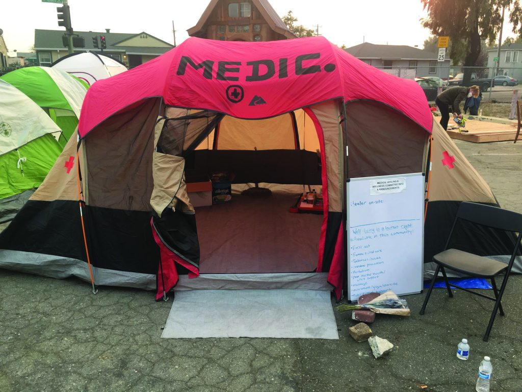 """A red tent with the word """"medic"""" on the top sits in the encampment."""
