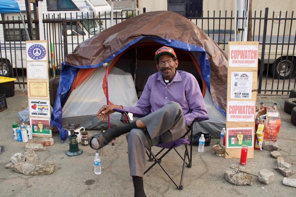Preston Walker sits outside his tent.