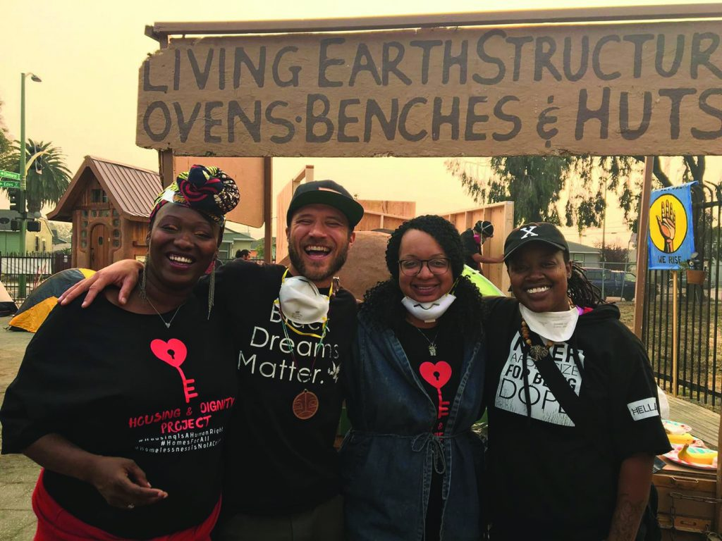 Candice Ender and a group of volunteers from East Oakland Collective take a break from helping to build HDV to smile for a photo.