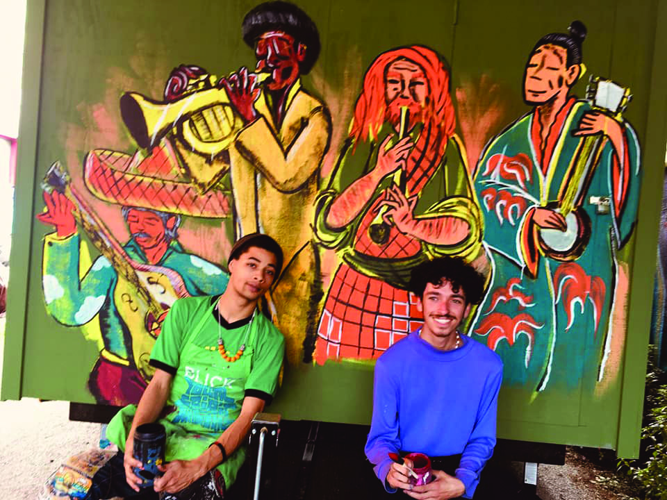 Omari Scott and Jordan Foster sit in front of a mural they painted on the side of one of the tiny houses.