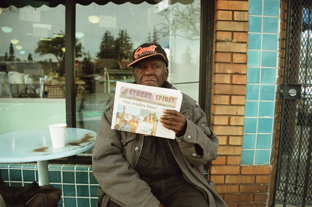 Art poses for a photo outside Sweet Adeline Bakeshop in Berkeley, where he used to sell Street Spirit.