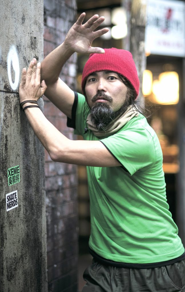 Nishi strikes a pose. He is wearing a green tshirt and a red beanie.