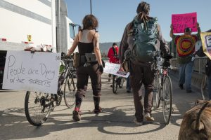 "Protestors walk with their bikes. A sign reads, ""People are dying on the streets."""