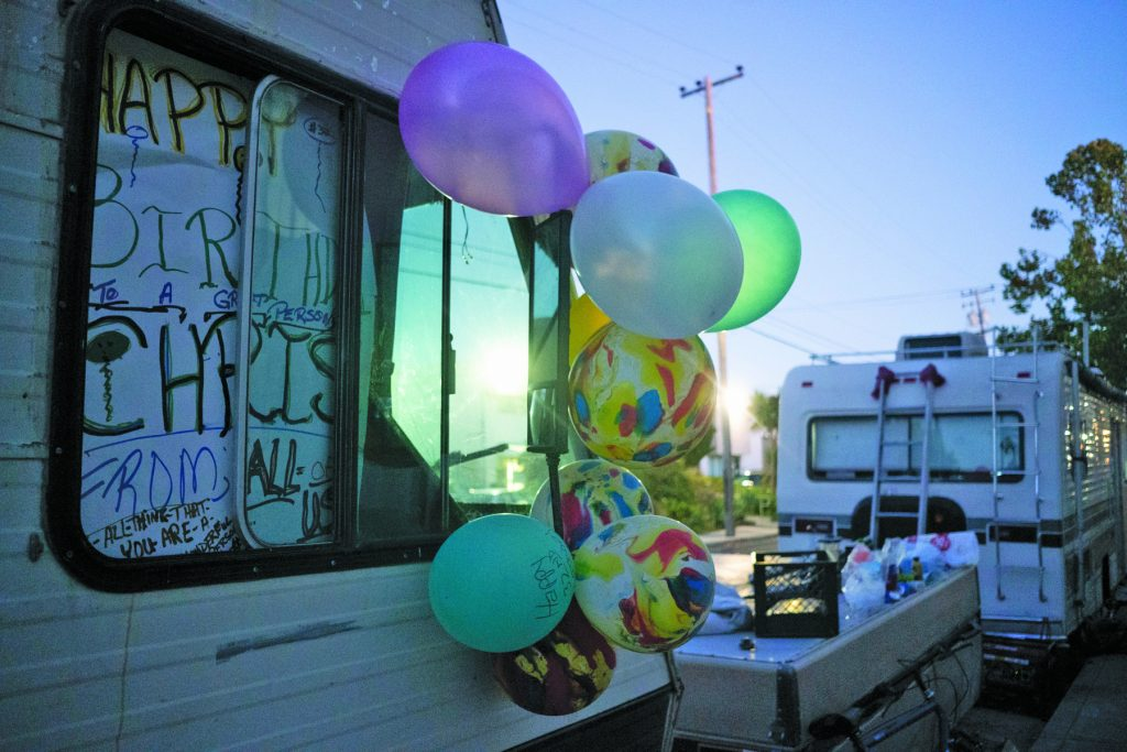 Balloons and birthday decorations hang on Chris Castle's recreational vehicle on 8th and Harrison streets in the Gilman District. Neighbors celebrate Castle's 29th birthday, cooking up in a barbecue and eating cake after the surrounding businesses have closed for the day.