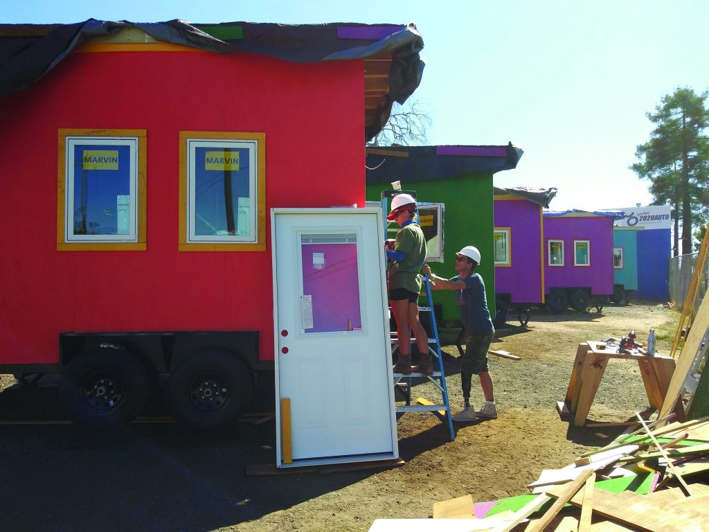 A row of multicolored tiny homes with volunteers working in the foreground.