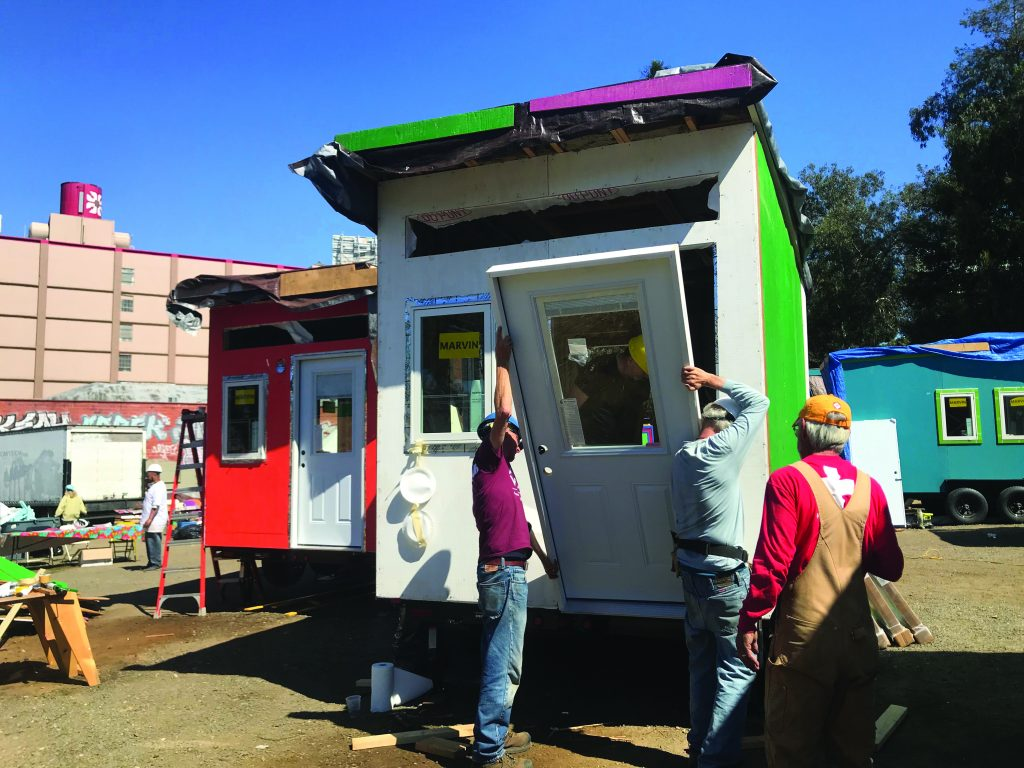 Volunteers put the door on one of the 15 tiny homes that was completed last spring.