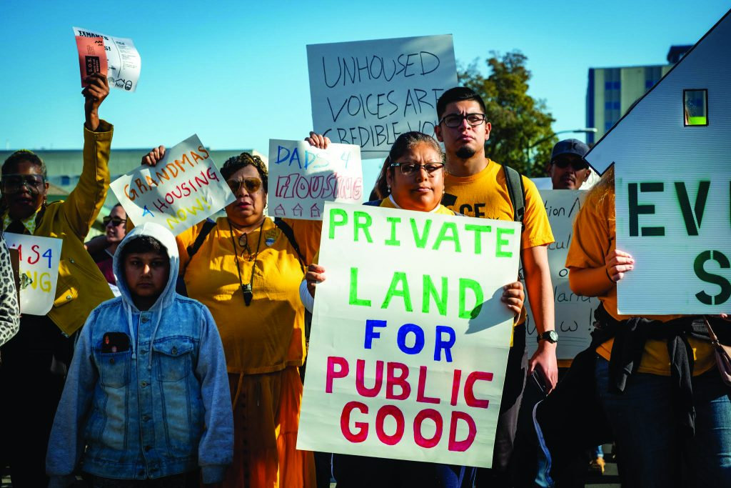 """Protestors hold signs that read, """"Private Land for Public Good"""" and """"Unhouses Voices are credible now"""""""
