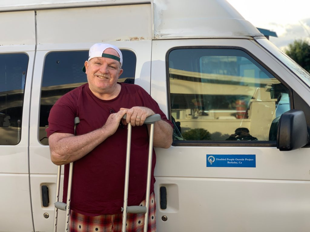 Danny McMullan stands with a Disabled People Outside Project van.