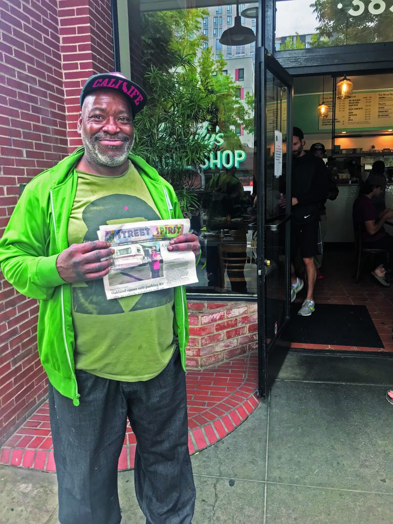 Hayes holds up a copy of Street Spirit outside Beauty's Bagels in Oakland.