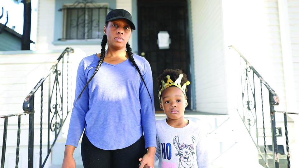 Dominique Walker stands with her daughter outside the house they occupied on Magnolia Street.